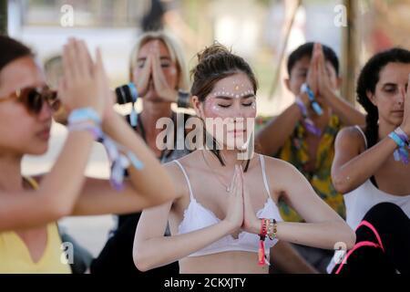 People do yoga at Wonderfruit art festival in Pattaya, Thailand, December 15, 2018. REUTERS/Ann Wang - Stock Photo