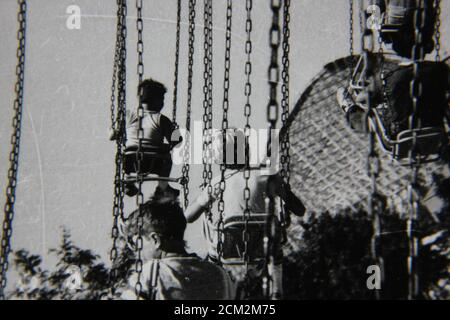 Fine 70s vintage black and white photography of kids riding a swing carousel, wave swinger, yo-yo, Chair-O-Planes, Dodo, or swinger. - Stock Photo