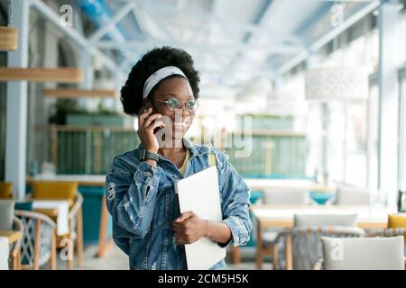 Cute dark skinned female entrepreneur holding digital tablet, making call while visiting coffee shop, inviting a candidate to a job interview.