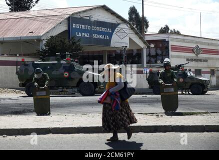 A woman walks past soldiers standing guard outside a power plant that supplies La Paz with gasoline, diesel and cooking gas, in Senkata, El Alto, Bolivia November 20, 2019. REUTERS/David Mercado Stock Photo
