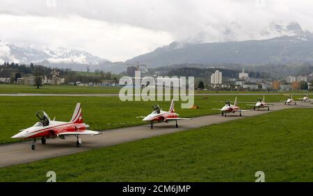Members of the Patrouille Suisse flight team of the Swiss Air Force roll in their Northrop F-5 ll Tiger fighting jets on a tarmac after performing during a media day of the Swiss Air Force at the airbase in the central Swiss town of Emmen April 17, 2015.   REUTERS/Arnd Wiegmann - Stock Photo
