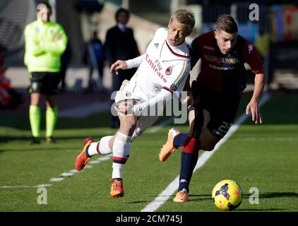 AC Milan's Keisuke Honda (L) of Japan challenges Nicola Murru of Cagliari during their Italian Serie A soccer match at the Sant'Elia stadium in Cagliari January 26, 2014.  REUTERS/Max Rossi (ITALY - Tags: SPORT SOCCER) - Stock Photo