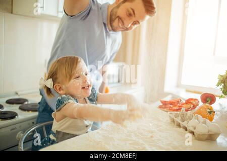 father and his son preparing a cake in the kitchen - Stock Photo