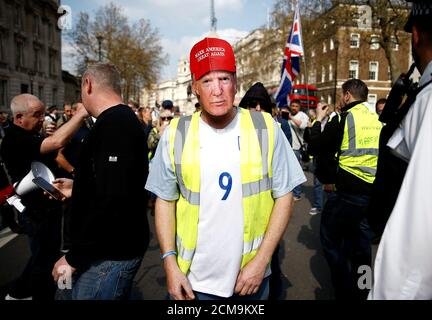 A pro-Brexit yellow vest protester, wearing a mask depicting U.S. President Donald Trump, demonstrates in London, Britain, March 30, 2019. REUTERS/Henry Nicholls - Stock Photo