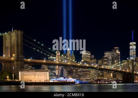 9/11 Tribute in Light. Brooklyn Bridge and Lower Manhattan illuminated at night. View from Main Street Park.
