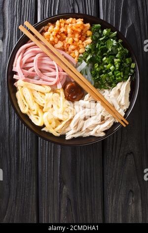 Bun Thang Vietnamese Noodle Soup with Chicken, Pork, Egg, herb and shrimp closeup in the plate on the table. Vertical top view from above - Stock Photo