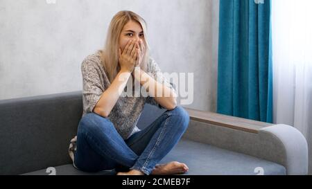 Pretty blonde woman covering mouth with hands with a shocked, she looks worried or scared.