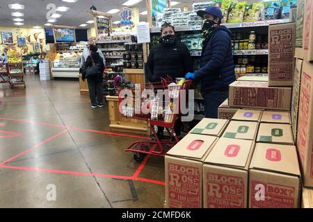 Shoppers wear face masks while practicing social distancing amid an outbreak of the coronavirus disease (COVID-19), at Trader Joe's in Emeryville, California, U.S., April 6, 2020. REUTERS/Shannon Stapleton - Stock Photo
