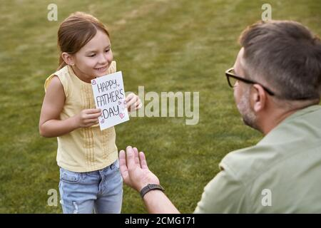 Surprise for my daddy. Cute little smiling girl, small daughter giving her father handmade postcard while celebrating Happy Fathers Day in park on a - Stock Photo