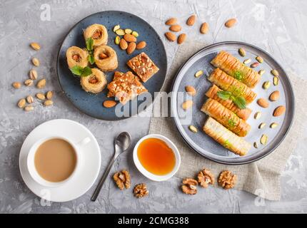 Set of various traditional arabic sweets: baklava, kunafa, basbus in  ceramic plates on a gray concrete background. top view, flat lay.