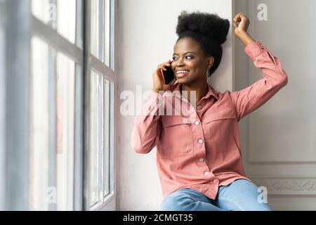 Happy African American millennial woman with afro hairstyle wear pink shirt, sitting on windowsill, smiling, taking on phone, looking at window. Black