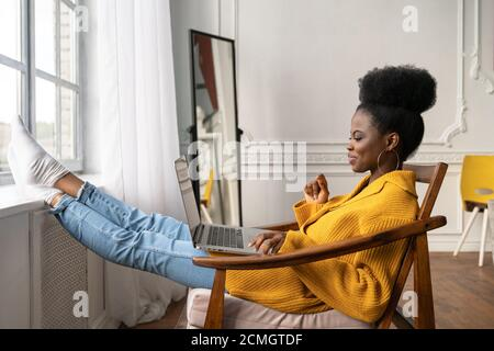 Happy African American woman freelancer with afro hairstyle wear yellow cardigan resting, sitting on chair, legs leaning on windowsill, remote studyin