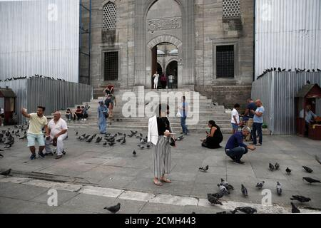 People stand outside the 17th-century Ottoman era New Mosque (Yeni Cami), in Istanbul, Turkey, July 18, 2016. REUTERS/Alkis Konstantinidis - Stock Photo