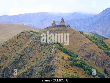 Incredible View of the Gergeti Trinity Church or Tsminda Sameba on the Hilltop with Large Group of Vositors, Stepantsminda Town, Georgia