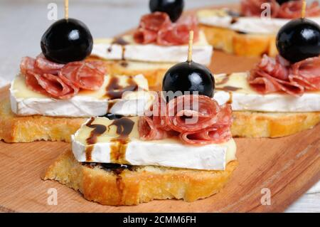 Snack from a toasted slice of baguette with soft under a noble white mold Cheese Brie, salami, a ber