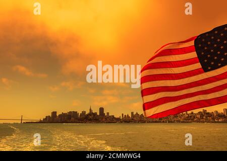 American flag with San Francisco Bay cityscape. Smoky orange sky for Californian fires in United States of America. Composition. - Stock Photo