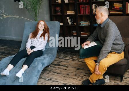 Side view of depressed red haired young woman talking about problems lying in comfortable armchair.