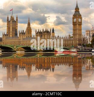 Big Ben and the Houses of Parliament on the River Thames with nice water reflection and cloudy sky.  London, UK