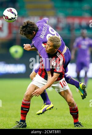 AC Milan's Keisuke Honda (bottom) challenges Fiorentina's Marcos Alonso Mendoza during their Serie A soccer match at San Siro stadium in Milan, October 26, 2014. REUTERS/Stefano Rellandini  (ITALY - Tags: SPORT SOCCER) - Stock Photo