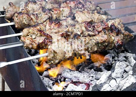 pieces of meat roasted on a spit over charcoal - Stock Photo