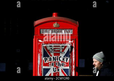 A pedestrian walks past an advertisement for 'Panicky in the UK' displayed on a phone box in the Soho district after they closed because of the spread of coronavirus disease (COVID-19), in London, Britain, March 22, 2020. REUTERS/Simon Dawson     TPX IMAGES OF THE DAY - Stock Photo