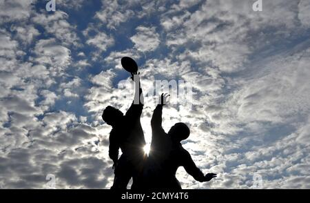 The sun rises behind a statue of rugby players reaching for the ball, outside Twickenham rugby stadium in west London September 17, 2015. The eight metre bronze sculpture created was created by artist Gerald Laing in 2010. The Rugby Union World Cup begins in Britain on Friday, with both the opening game and ceremony and final taking place at Twickenham.  REUTERS/Toby Melville