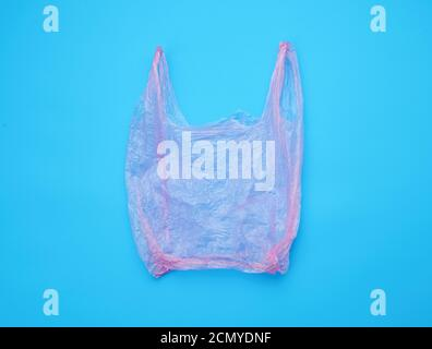 open empty plastic pink bag for products on a blue background
