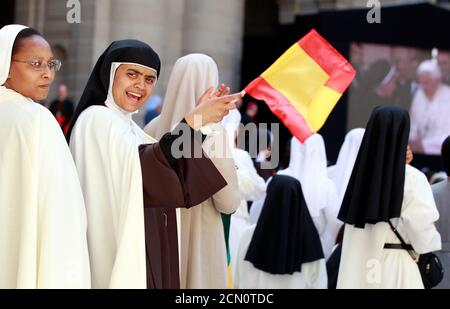 A nun waves a Spanish flag outside the monastery of El Escorial in San Lorenzo de El Escorial during the Pope Benedict XVI second day visit to Spain coinciding with the World Youth Day festivities August 19, 2011. Pope Benedict denounced economic structures that put profits ahead of people on Thursday at the start of a trip to recession-hit Spain where the costs of the pontiff's visit have sparked violent protests.   REUTERS/Tony Gentile   (SPAIN - Tags: RELIGION) - Stock Photo