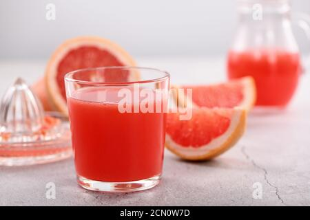 A glass of freshly made grapefruit juice and slices of fresh fruit on a light concrete background. H