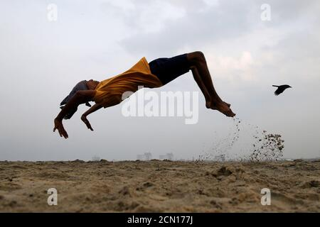 A boy practices somersaulting as he exercises at a beach in Kochi, India, March 11, 2019. REUTERS/Sivaram V - Stock Photo