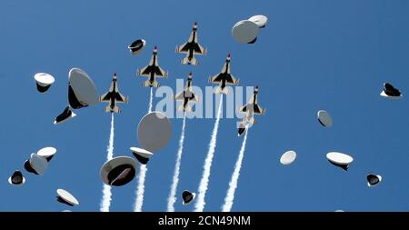 The Thunderbirds perform a fly-over as graduates from the Air Force Academy toss their hats in the air at the conclusion of their commencement ceremony in Colorado Springs, Colorado, U.S., June 2, 2016. REUTERS/Kevin Lamarque     TPX IMAGES OF THE DAY - Stock Photo