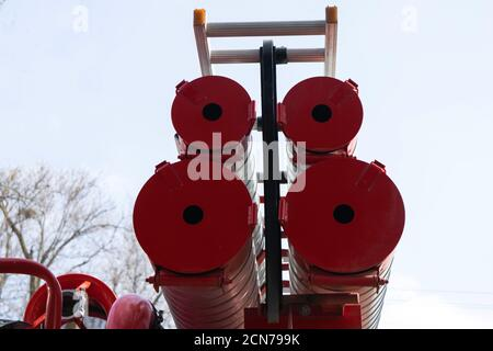 a fire truck, rear view of canisters for transporting suction hoses with fire escapes attached to them