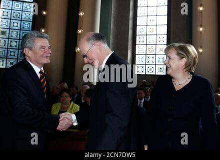 Opposition Social Democrats (SPD) and Greens presidential candidate Joachim Gauck (L) shakes hands with Bundestag President Norbert Lammert (2nd L) as German Chancellor Angela Merkel watches before a church service before the German presidential election in the St. Hedwigs Cathedral in Berlin June 30, 2010. Germany?s federal assembly voted on Wednesday whether to elect Chancellor Merkel's conservative candidate, Lower Saxony state premier Christian Wulff, or the centre-left opposition nominee, Protestant pastor Gauck. REUTERS/Thomas Peter  (GERMANY - Tags: POLITICS RELIGION ELECTIONS) - Stock Photo