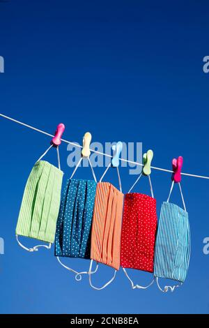colourful face masks hanging on a washing line - Stock Photo