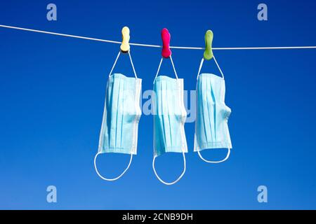 Surgical masks hanging on a washing line - Stock Photo
