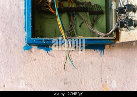 Old dismantled and rusty electrical panel assembly on an abandoned and destroyed factory against a backdrop of chaos. Destruction and vandalism. - Stock Photo