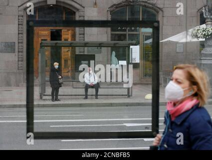 People wearing protective face masks wait at a public transport stop as a pedestrian walks nearby amid the coronavirus disease (COVID-19) outbreak in central Kiev, Ukraine June 2, 2020. REUTERS/Gleb Garanich - Stock Photo