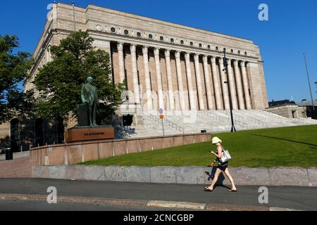 A woman walks past Finland's Parliament house in Helsinki, Finland July 16, 2018. Picture taken July 16, 2018.  REUTERS/Ints Kalnins - Stock Photo
