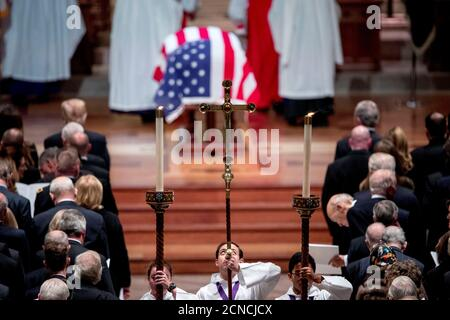 The flag-draped casket of former President George H.W. Bush is visible as altar servers line up in the center isle during Bush's State Funeral at the National Cathedral, Wednesday, Dec. 5, 2018, in Washington. Andrew Harnik/Pool via REUTERS