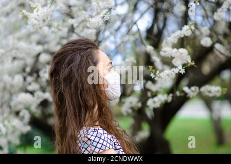 Girl, young woman in a protective sterile medical mask on her face in the spring garden. Pollution, virus, pandemic coronavirus concept. Stock Photo