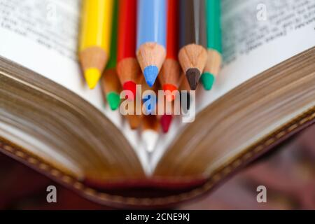 Colored pencils on a Bible, Catechism, France, Europe Stock Photo