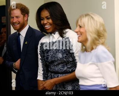 U.S. first lady Michelle Obama (C), Dr. Jill Biden, wife of Vice President Joe Biden, and Britain's Prince Harry tour the USO Warrior and Family Center at Fort Belvoir, Virginia October 28, 2015. REUTERS/Kevin Lamarque - Stock Photo