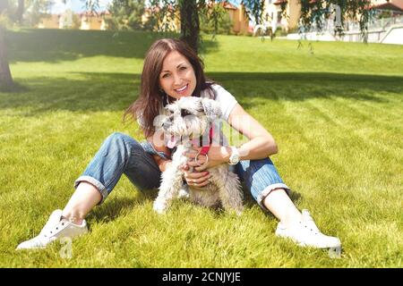 Pretty adult caucasian happy woman resting in the park on a sunny day with her beloved dog. Female lies on the grass, smiling an