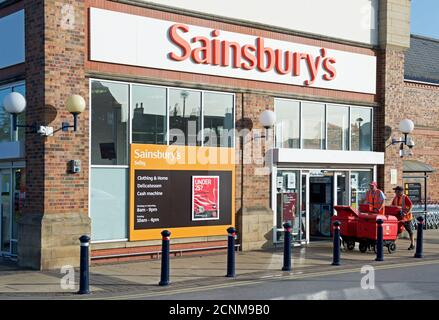 Postmen passing the entrance of Sainsbury's supermarket in Selby, North Yorkshire, England UK - Stock Photo