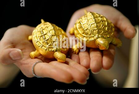 An employee holds replicas of turtles made of gold during a photo opportunity at a jewellery shop in Seoul August 2, 2011. Gold edged higher on Tuesday, supported by a purchase of 25 tonnes of the precious metal by South Korea's central bank, while investors watched the outcome of a vote on the U.S. debt deal. South Korea's central bank said it bought the gold between June and July to diversify its foreign reserves despite high prices, marking its first purchase in more than a decade and taking its total gold holdings to 39.4 tonnes.   REUTERS/Truth Leem (SOUTH KOREA - Tags: BUSINESS) - Stock Photo