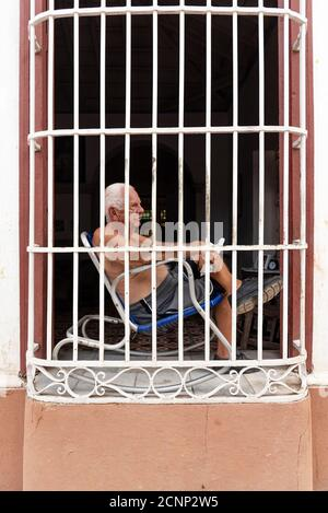 August 26, 2019: Man sitting in front of his window with bars. Trinidad, Cuba - Stock Photo