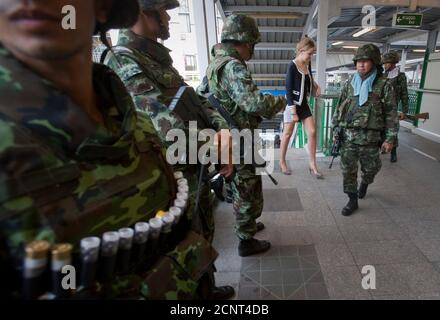A foreign woman walks past Thai army soldiers standing guard on a walkway at the Asok skytrain station in Bangkok April 28, 2010. Protesters in Thailand pushing for early elections threatened mobile rallies across Bangkok on Wednesday in defiance of a state of emergency, which would increase the risk of clashes with troops or rival protest groups.  REUTERS/Vivek Prakash (THAILAND - Tags: POLITICS CIVIL UNREST MILITARY IMAGES OF THE DAY) Stock Photo