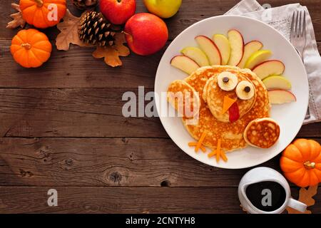 Cute Thanksgiving turkey pancakes. Top view corner border against a rustic wood background with copy space. - Stock Photo