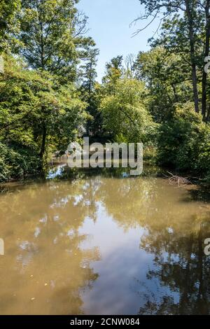 River with brown water along the countryside - Stock Photo