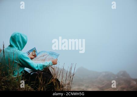 Traveler with a map sitting on the hill of a mountain in front of a gorgeous panorama view to the valley. - Stock Photo